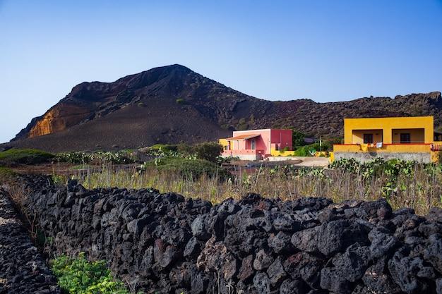 典型的なカラフルな家と溶岩石で建てられた乾いた石の壁のあるリノザ島の特徴的な景色