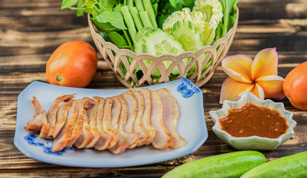 Charcoal-boiled pork neck with many vegetable on wooden table background.