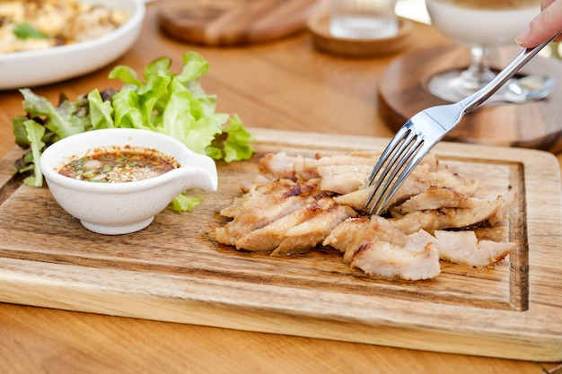 소스를 곁들인 숯불 삶은 돼지 목은 매콤한 신맛이 태국에서 인기있는 전채입니다. 구운 돼지 고기 스테이크 태국 음식