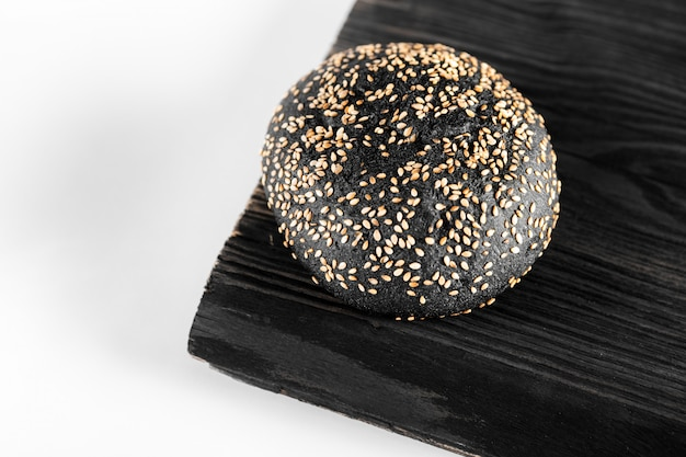 Charcoal bread, black bread isolated on wood background.
