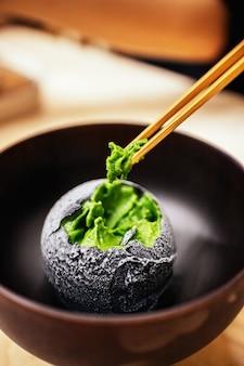 箸でつまむ緑茶のアイスクリームを炭でコーティングしたもの。