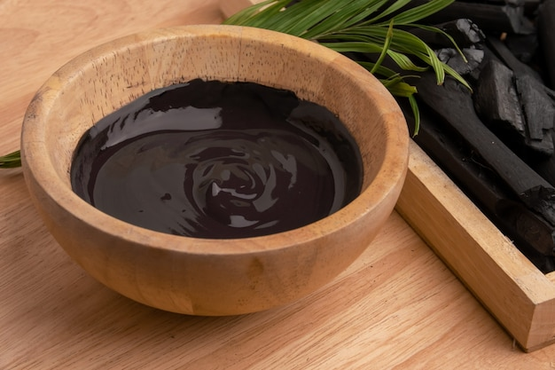 Charcoal cream in wooden bowl for facial spa treatment.