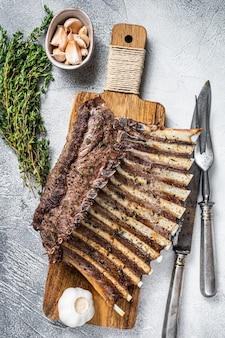 Французская стойка с ребрышками ягненка, приготовленная на углях, на разделочной доске. белый фон. вид сверху.