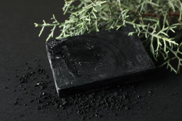 黒の背景に木炭石鹸とthujaの枝