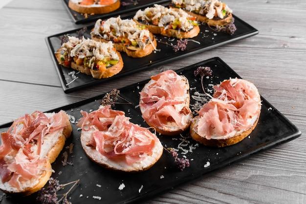 豚肉とチーズボード、硬化肉とさまざまな種類のチーズ。黒いプレートの燻製肉。おいしいパルメザンチーズ、ドルブル、ソフトチーズ、カマンベールチーズのフードボード。