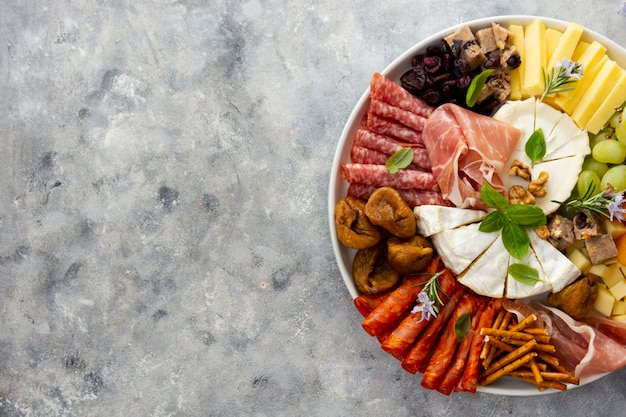Charcuterie assortment, variety of cheeses and salami, prosciutto and dried fruits, figs, apricots, cranberries. copy space.