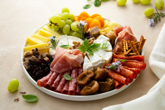 Charcuterie assortment, variety of cheeses and salami, prosciutto and dried fruits, figs, apricots, cranberries. top view