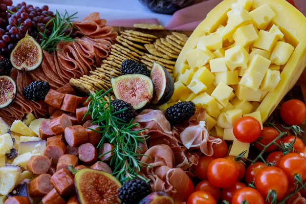 Charcuterie board with assortment of cheese, fruits and deli. close up.