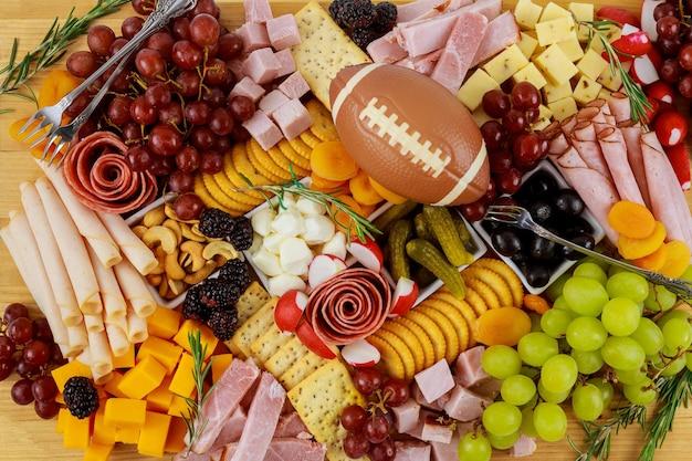 チーズ、ブドウ、ハム、クラッカーを添えたシャルキュトリーボード。アメリカンフットボールの食事。