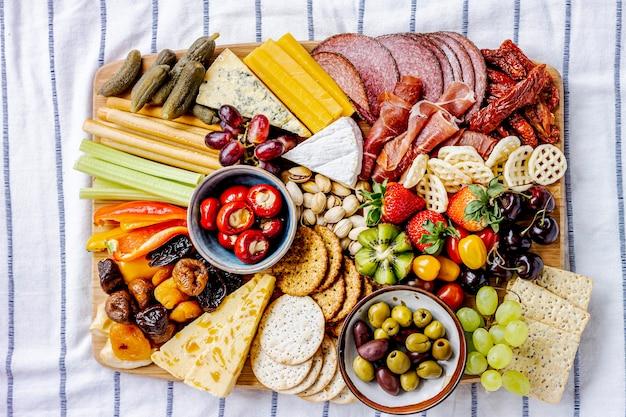 Tagliere di salumi con affettati, frutta fresca e formaggio close up