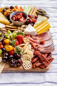 Charcuterie board with cold cuts, fresh fruits and cheese close up