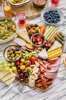 Tagliere di salumi con affettati, frutta fresca e formaggio su telo da picnic