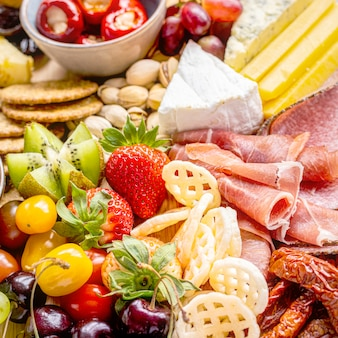 Charcuterie board with cold cuts, fresh fruits and cheese