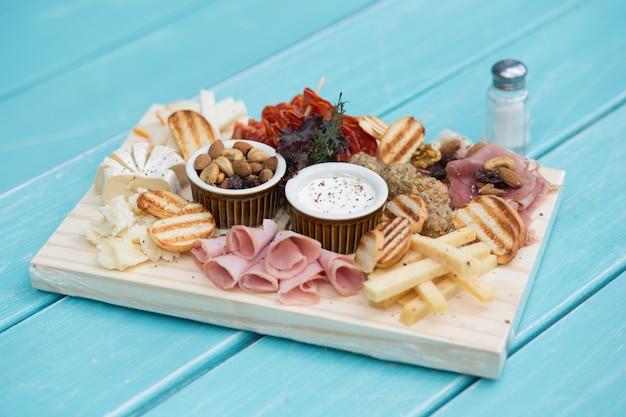 프로슈토, 카피 콜라 및 기타 이탈리안 델리 경화 고기를 곁들인 샤 르쿠 테리 보드. 나무 테이블과 하늘색 테이블.