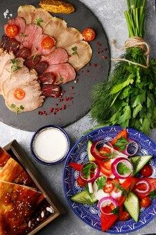 シャルキュトリー、肉の盛り合わせ、野菜プレートのサマーサラダ。アンティパスト。ハム、生ハム、ベーコンのスモーク プレート トップ ビュー.