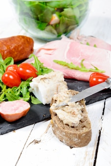 Charcuterie plate with bread and tomatoes on wooden board
