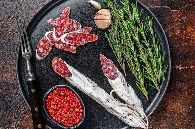 Charcuterie with fuet salami sausage and rosemary on a plate. dark background. top view.
