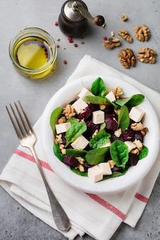 Мангольд, руккола, свекла, сыр рикотта и салат из грецких орехов с оливковым маслом в старинной керамической тарелке на серой бетонной поверхности