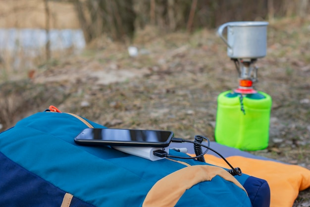 보조 배터리로 여행 중에 스마트폰을 충전하세요. 휴대용 충전기는 관광 가스 버너와 숲을 배경으로 전화를 충전합니다.