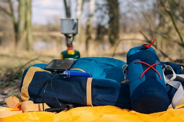 파워 뱅크를 가지고 여행하는 동안 스마트 폰을 충전하십시오. 휴대용 충전기는 관광 가스 버너와 숲을 배경으로 휴대폰을 충전합니다.