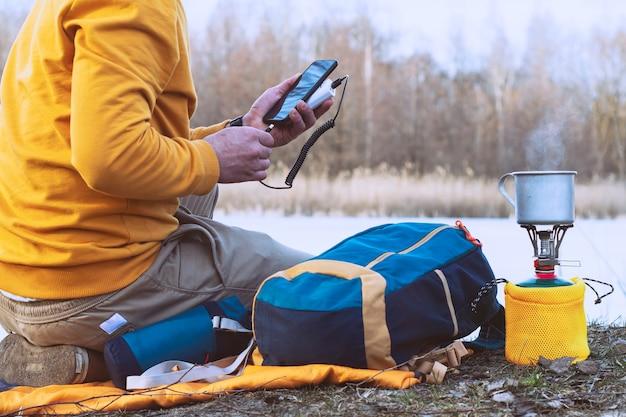 파워 뱅크를 가지고 여행하는 동안 스마트 폰을 충전하십시오. 관광객이 휴대용 충전기를 손에 들고 관광 가스 버너, 호수, 숲을 배경으로 전화기를 충전합니다.