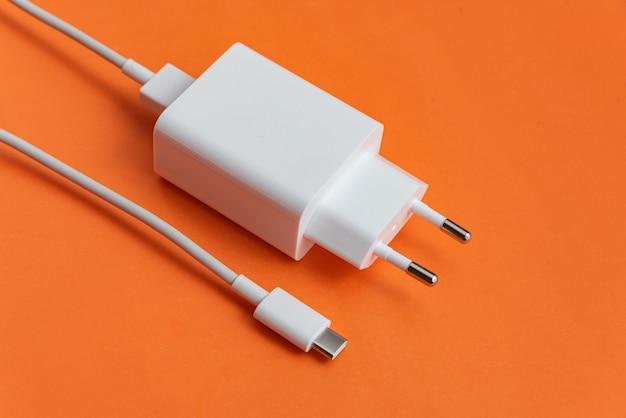 オレンジ色の背景に充電器とusbケーブルタイプc