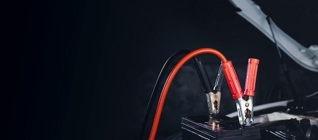 충전기 케이블을 자동차 배터리에 클램핑하여 축전지 충전 및 복사 공간이 있는 검정색 배경