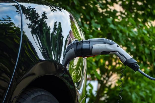 녹색 환경 배경에 전기 자동차에 충전기 플러그