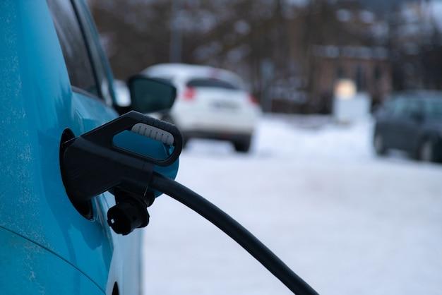 Вилка зарядного устройства вставлена в электромобиль на фоне снежной зимы