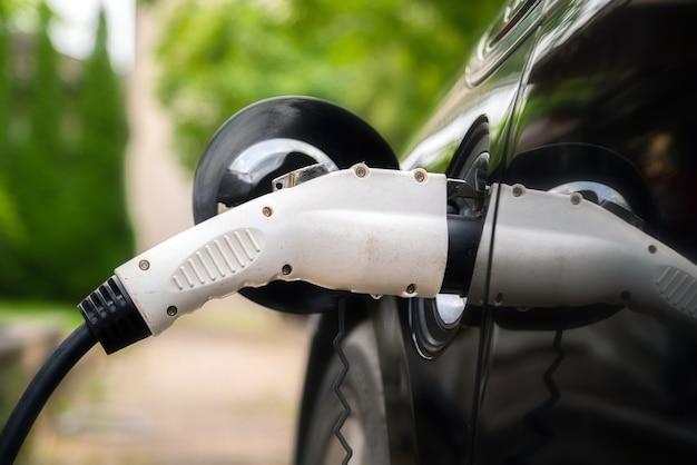 Вилка зарядного устройства вставлена в электромобиль.