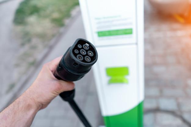 Зарядный кабель в руке у зарядной станции для электромобилей крупным планом.