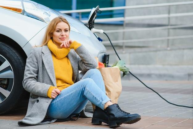 전기 주유소에서 전기 자동차 충전. 차로 여자입니다. 프리미엄 사진