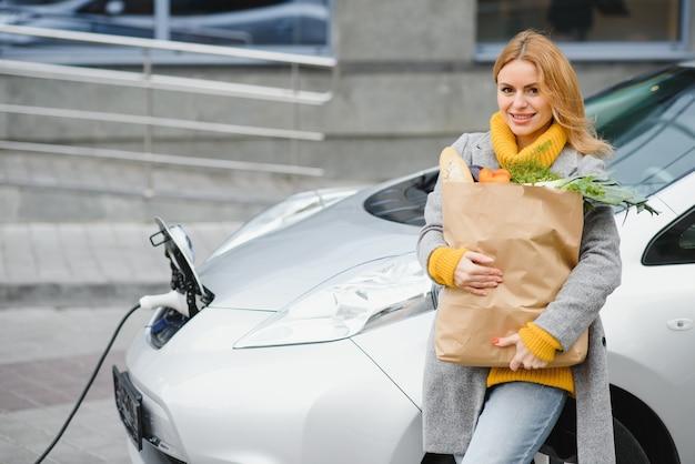 전기 주유소에서 전기 자동차 충전. 차 옆에 서있는 여자.