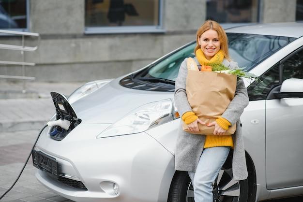 전기 주유소에서 전기 자동차 충전. 차 옆에 서있는 여자. 프리미엄 사진