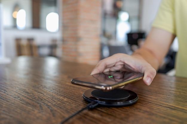 테이블의 무선 충전 장치로 휴대폰 배터리를 충전합니다. 충전 패드에서 스마트 폰 충전. 무선 충전기 근처 휴대 전화 현대적인 라이프 스타일 개념입니다.