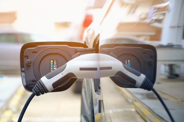자동차의 미래 거리에서 현대 전기 자동차 배터리를 충전 하이브리드 자동차 충전 전기 자동차에 연결 된 전원 공급 장치 닫습니다. 자동차 연료의 새로운 시대.