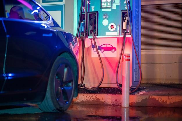 충전기와 검은색 전기 자동차의 일부가 있는 충전 더미