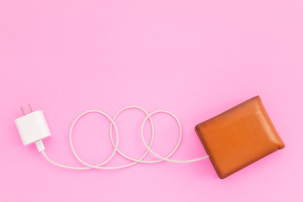 Charging the power to financial concept : top view white charger cable connect to brown wallet