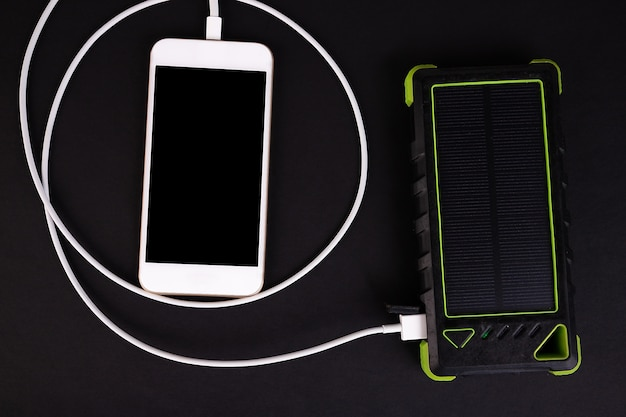 Charging smartphone using a power bank on a black table