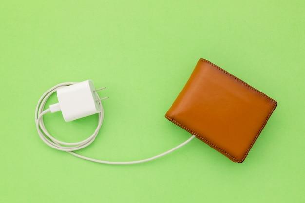 財務コンセプトへの電力の充電:上面の白い充電器ケーブルを茶色の財布に接続
