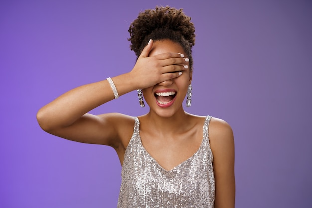 Charismatic african girl in glittering silver evening dress close eyes palm smiling laughing happily waiting surprise party celebrating birhday wanna receive gift anticipating near blue background.