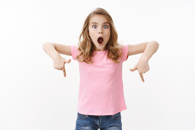 분홍색 티셔츠를 입은 카리스마 넘치는 귀여운 금발의 유럽 소녀, 놀라운 것을 설명하고, 놀라고 흥분한 표정을 짓고, 입을 크게 벌리고, 아래를 가리키고, 아래쪽 프로모션을 나타냅니다.
