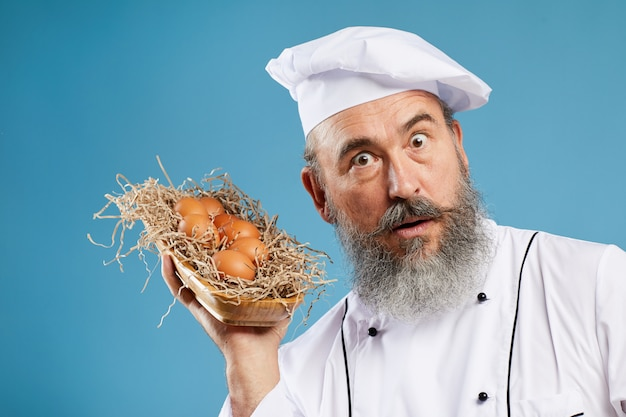 Charismatic bearded chef holding eggs