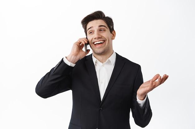 スマートフォンで話し、笑い、活発な電話をかけ、白い壁に黒いスーツを着て幸せに立っているカリスマ的なビジネスマン