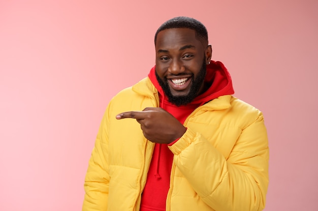 Charismatic carefree handsome black bearded guy in yellow jacket laughing friendly look camera chat pointing left show cool place hang out standing joyful pink background talking having fun