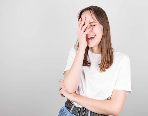 Charismatic carefree joyful friendly brunette woman in a white t-shirt and jeans loves to laugh out loud without hiding emotions