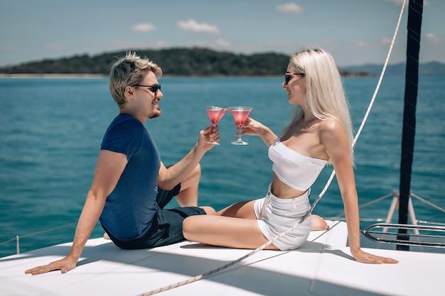 カリスマ的な陽気なモデルの男性と女性は、クリスタルガラスでカクテルを飲みながら、かわいい小さな話を楽しんでいます。