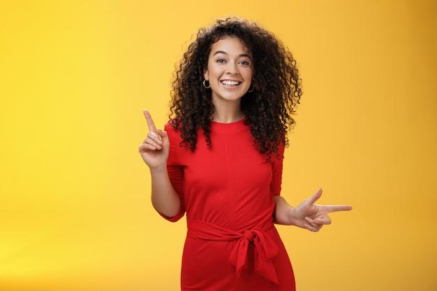 カリスマ的なキュートで幸せな若い縮れ毛のヨーロッパ人女性が赤いドレスを着て踊り、上向きと右向きで、カメラに向かって選択、決定、笑顔を提示するように横向きに表示します。
