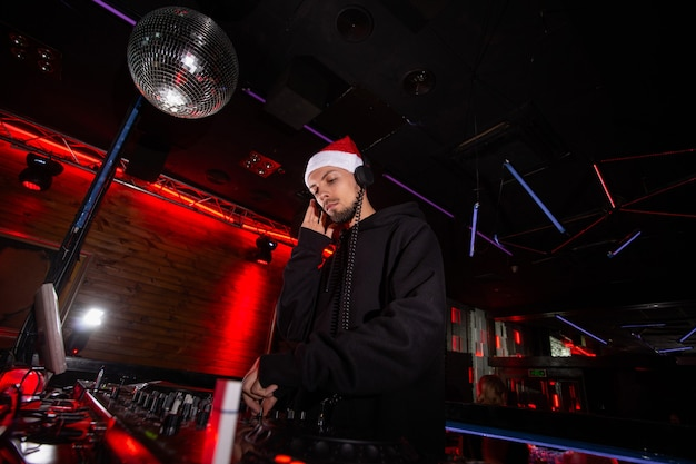 Charismatic disc jockey in red santa claus hat, headphones and hoody plays music at dj turntables. christmas party