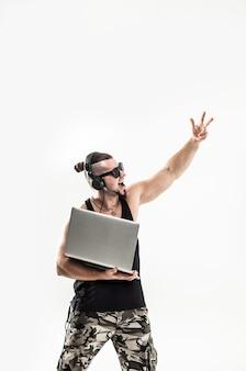 Харизматичный ди-джей - рэпер в наушниках и с ноутбуком.